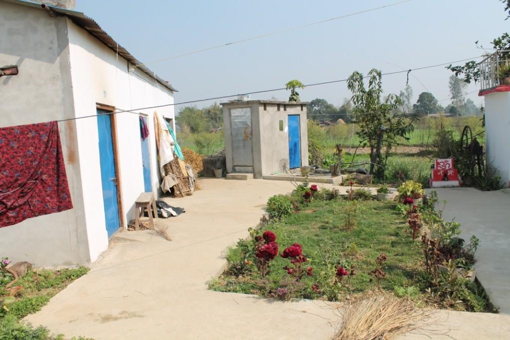 Das kleine graue Häuschen in der Mitte des Bildes beherbergt hinter der silbernen Tür die Toilette, und hinter der blauen das Badezimmer. Das Gebäude links war zum Teil Stall für den Büffel, und zum Teil einfach Abstell- und Lagerraum.